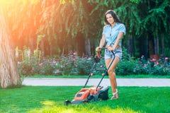 Mähender Rasen der Frau im Wohnhinteren garten Stockbild