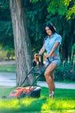 Mähender Rasen der Frau im Wohnhinteren garten Lizenzfreies Stockfoto