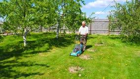 Mähender Rasenmäher des alten Mannes im schönen Garten stock video