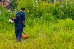 Mähendes Gras des Mannes mit einem Rasenmäher Lizenzfreie Stockfotografie