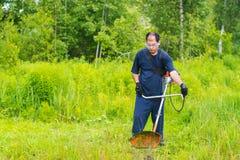 Mähendes Gras des Mannes mit einem Rasenmäher Stockfoto