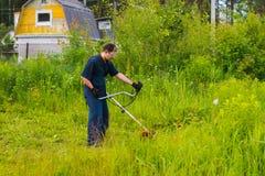 Mähendes Gras des Mannes mit einem Rasenmäher Lizenzfreies Stockbild