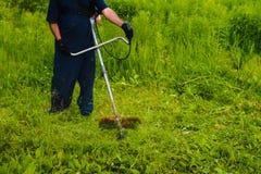 Mähendes Gras des Mannes mit einem Rasenmäher Lizenzfreie Stockfotos