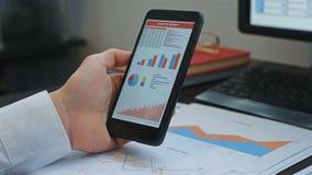 MäklareLooking At Stock graf på mobiltelefonen stock video