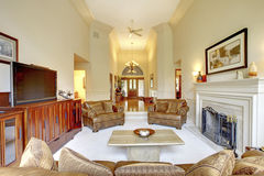 Mäktig vardagsrum för högt tak i lyxigt hus Sikt av hallet med ingångsdörren royaltyfria bilder