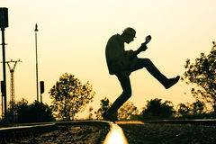 Män är jumpig på spår med gitarren i mitt--luft royaltyfri fotografi