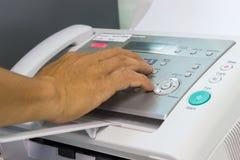Män använder en faxmaskin i kontoret Arkivbild