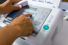 Män använder en faxmaskin i kontoret Arkivbilder
