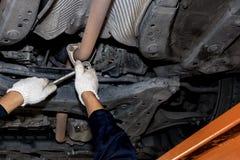 Män använder en skruvmejsel och en öppen olja för bilreparationsskiftnyckel royaltyfria foton