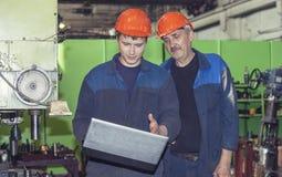 Män arbetar på den gamla fabriken för installationen av utrustning royaltyfri foto
