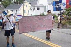 Män bär undertecknar Wellfleeten 4th Juli ståtar in i Wellfleet, Massachusetts Arkivbild