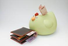 Män bryner plånboken med spargrisen Royaltyfria Bilder