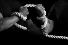 Män drar åt ett rep på en svart bakgrund arkivbild