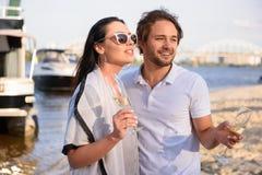 Män dricker champagne med hans par på stranden royaltyfri fotografi