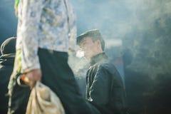 Män för etnisk minoritet röker, på den gamla Dong Van marknaden royaltyfria foton