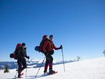 Män går i snöskor i bergen royaltyfri bild