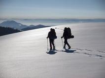 Män går i snöskor i bergen royaltyfri foto