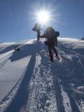 Män går i snöskor i bergen arkivbilder