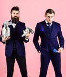 Män i dräkt, affärsmän med kruset som är full av kassa och kreditkort, rosa bakgrund bankkontobegrepp Den mogna mannen önskar arkivfoto