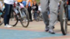 Män i gråa gymnastikskor med cykeln går in mot kamera Många cyklister på ett område Folkmassa i sportswear Lowen metar beskådar stock video
