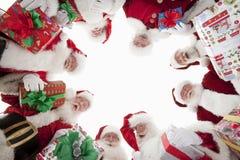 Män i Santa Claus Outfits Forming Huddle fotografering för bildbyråer