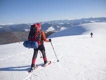 Män i snöskor går i bergen royaltyfria foton
