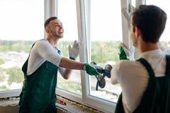 Män installerar ett fönster arkivfoton