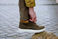 Män korrigerar skosnöre Arkivfoto