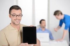 Män med den digitala minnestavlan. Lycklig ung affärsman som rymmer en siffra Fotografering för Bildbyråer