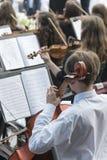Män med en violoncell i en orkester royaltyfri fotografi
