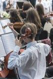 Män med en violoncell i en orkester Vertikalt foto arkivfoton