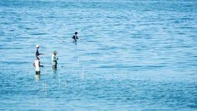 Män med metspöet står i vatten av Taungthaman sjön Arkivfoto