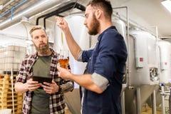 Män med pipettprovning tillverkar öl på bryggeriet Arkivbild