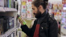 Män med skägget och långt hår som väljer antiperspiranten i supermarket stock video