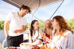 Män med tre härliga flickor dricker champagne på yachten royaltyfri bild