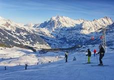 Män och kvinnor skidar på och snowboards nära kabeljärnväg på winte Royaltyfri Fotografi