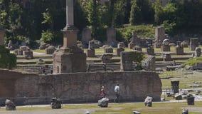 Män och kvinnor som beskådar stenen, fördärvar av forntida Roman Forum i Italien, ultrarapid arkivfilmer