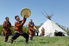 Män och kvinnor som dansar med en tamburin på gräset på en bakgrundsyaranga Kamchatka Ryssland Royaltyfri Bild