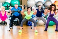 Män och kvinnor som lyfter skivstången i idrottshall Fotografering för Bildbyråer