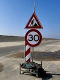 Män på arbetstecknet på den tomma vägen Varning som kör långsamt royaltyfria bilder