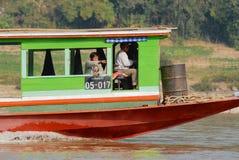 Män rider det långa fartyget vid Mekonget River i Luang Prabang, Laos Royaltyfri Bild