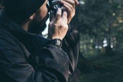 Män som är turist- i höstberg Grönt trä solsken Klocka kamera arkivfoto