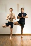 män som öva yoga för två vertical Arkivfoto