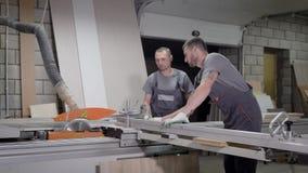 Män som arbetar på det wood anseendet för bitande maskin i likformig i fabrik lager videofilmer