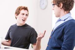 Män som argumenterar på deras arbetsplats Arkivfoto