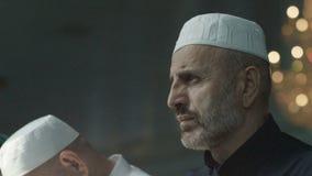 Män som bär den muslimska huvudbonaden, ber i den Ingusjetien moskén arkivfilmer