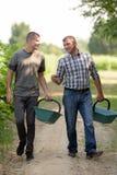 Män som bär deras korg, medan gå samtal fotografering för bildbyråer