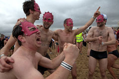 Män som bär maskeringar på stranden, Belgien Royaltyfria Foton