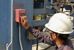 Män som bär säkerhetshjälmar, trycker på brandlarm arkivfoton
