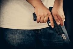 Män som bär t-skjortor, jeans som står rymma ett vapen i huset royaltyfri foto